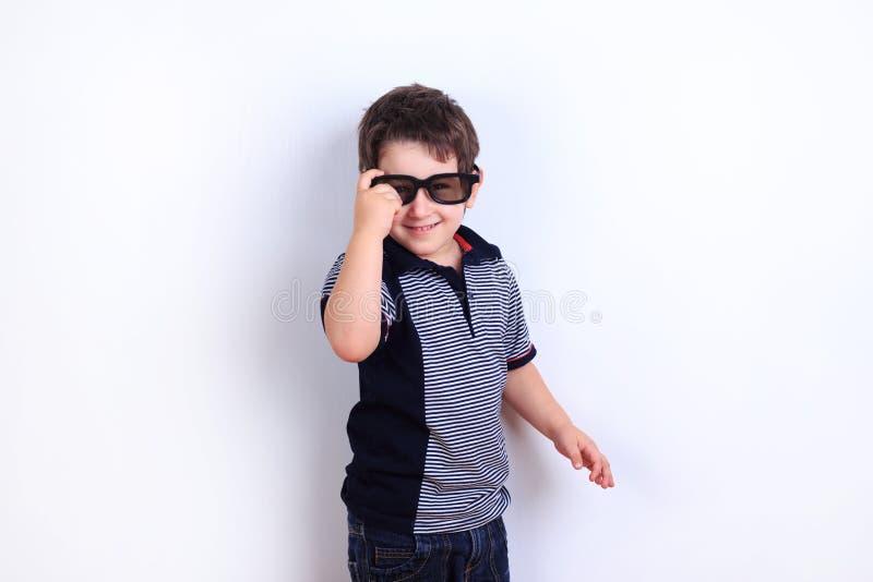 Óculos de sol vestindo do rapaz pequeno engraçado bonito, tiro do estúdio no branco imagens de stock royalty free