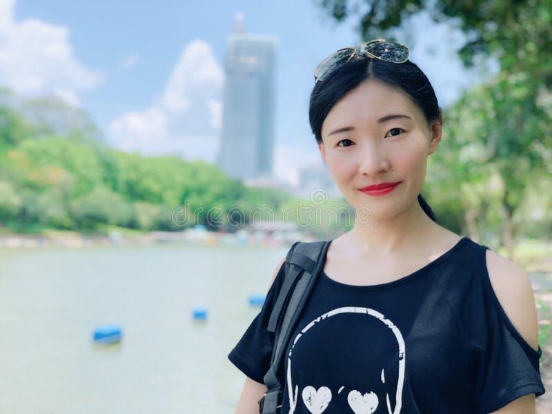 Óculos de sol vestindo e sorriso de um retrato asiático da jovem mulher foto de stock