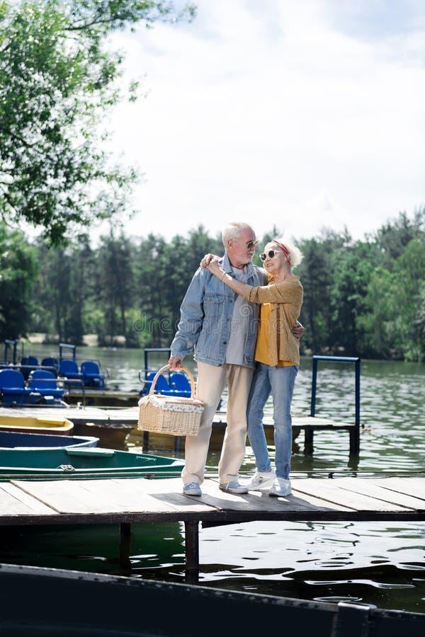 Óculos de sol vestindo envelhecidos da esposa e do marido que estão perto do rio imagens de stock royalty free