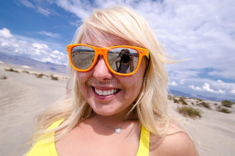 Óculos de sol vestindo fêmeas louros da praia nas dunas de areia do Mesquite no parque nacional de Vale da Morte Califórnia imagem de stock royalty free