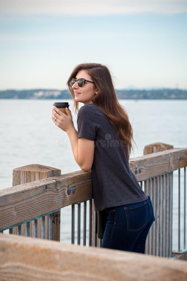 Óculos de sol vestindo de uma mulher moreno nova bonita com um café em um passeio à beira mar do perto do oceano que aprecia a vi foto de stock royalty free
