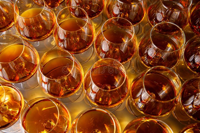 Óculos estilosos com cognac ou uísque na mesa na catering de eventos imagem de stock royalty free