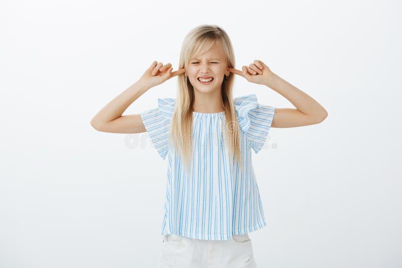 Ódio da menina quando argumentação dos pais Displeased irritou a jovem criança com cabelo louro na blusa azul, cobrindo as orelha foto de stock royalty free