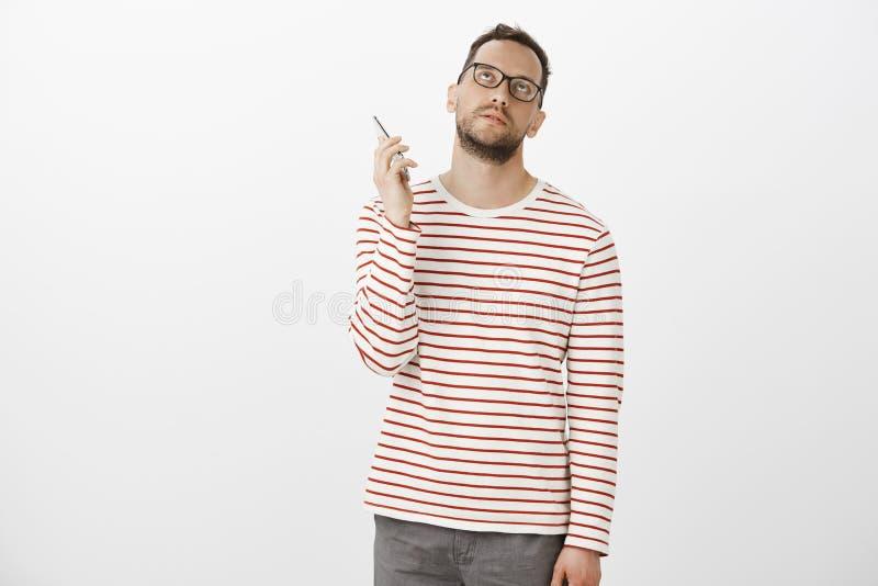 Ódio que pendura no telefone Bothered irritou o homem europeu atrativo nos vidros, olhando furados acima e guardando o smartphone fotos de stock royalty free