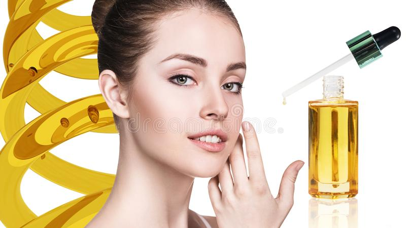 Óleo cosmético que aplica-se na cara da jovem mulher imagens de stock royalty free