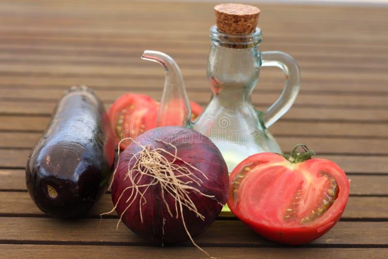 Óleo da beringela, da cebola vermelha, do tomate e o de vidro fotografia de stock