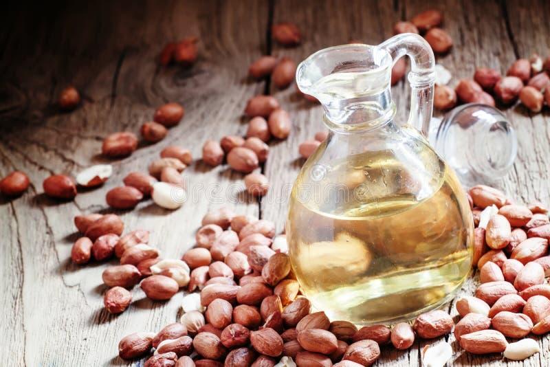 Óleo de amendoim em um frasco de vidro, amendoins crus, backgroun de madeira do vintage fotografia de stock royalty free