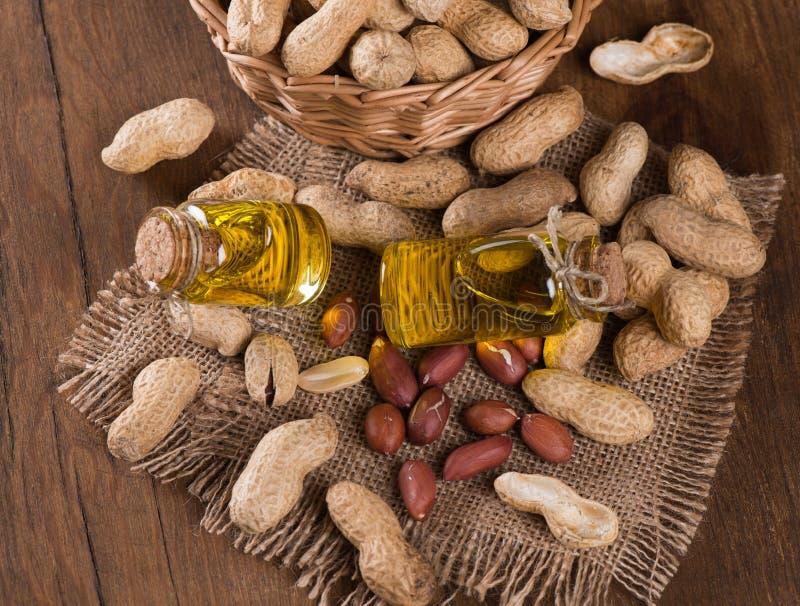 Óleo de amendoim em uma garrafa de vidro com amendoins crus imagens de stock