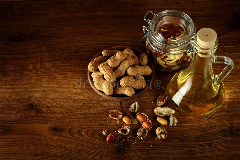 Óleo de amendoim na garrafa e em porcas secas na tabela de madeira Vista superior fotografia de stock
