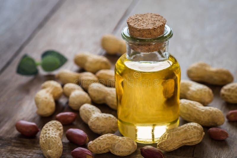 Óleo de amendoim na garrafa de vidro e nos amendoins na tabela de madeira imagens de stock