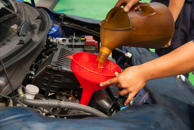 Óleo de derramamento de conservação do mecânico do carro ao motor imagem de stock royalty free