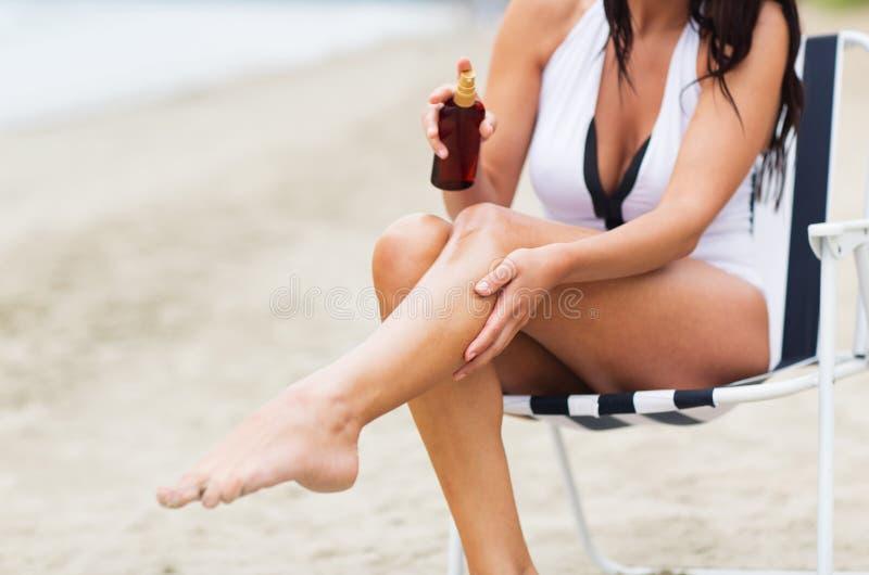 Óleo de pulverização da proteção solar da mulher a sua pele na praia imagens de stock royalty free