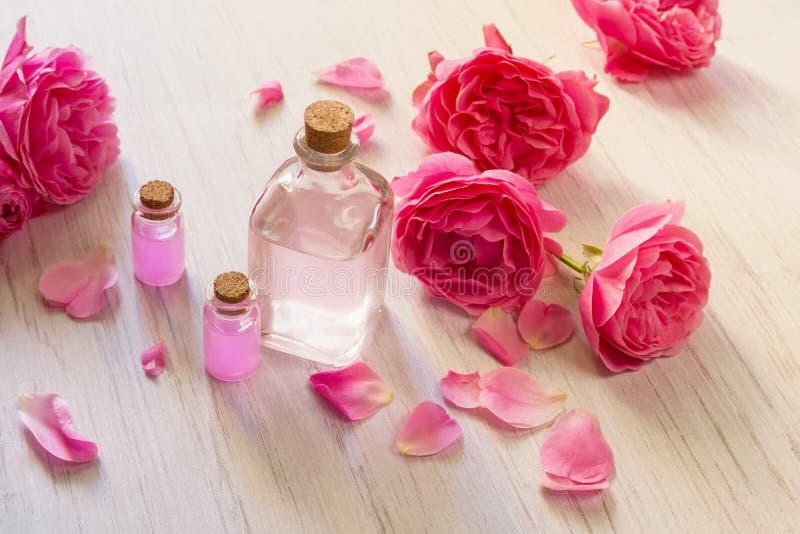 Óleo de Rosa nas garrafas de vidro e nas pétalas cor-de-rosa da flor no fundo de madeira branco imagens de stock