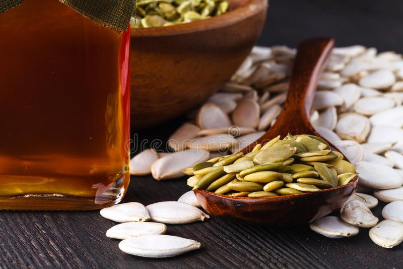 Óleo de semente da abóbora em uma garrafa de vidro em uma tabela de madeira tradicional rústica marrom fotografia de stock
