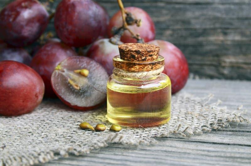 Óleo de semente da uva em um frasco de vidro e em umas uvas frescas na tabela de madeira velha Garrafa do óleo de semente orgânic fotografia de stock royalty free
