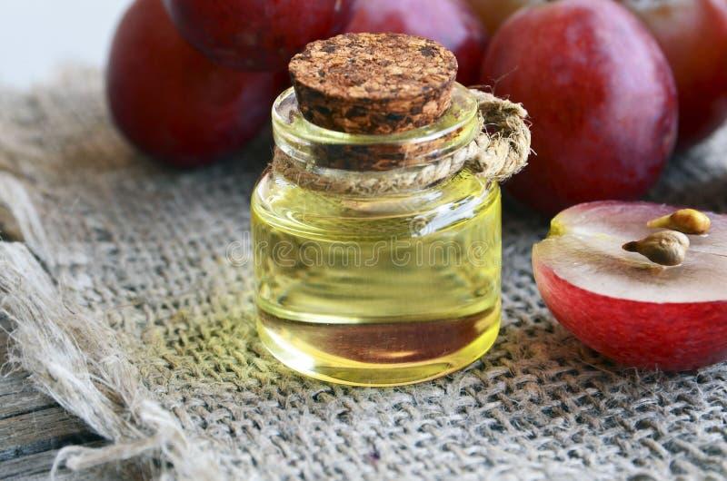 Óleo de semente da uva em um frasco de vidro e em umas uvas frescas no fundo de pano de serapilheira Garrafa do óleo de semente o imagens de stock