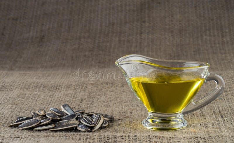 Óleo de semente do girassol em um barco de molho de vidro e um punhado de sementes de girassol fotografia de stock royalty free