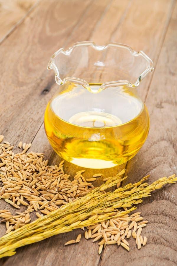 Óleo do farelo de arroz no vidro de garrafa e em arroz unmilled no backgr de madeira fotografia de stock