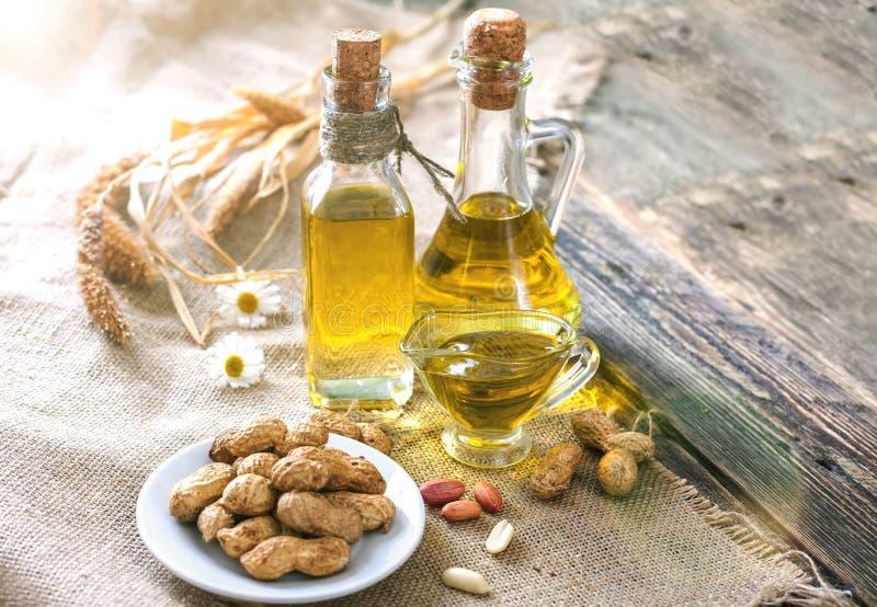 Óleo e amendoins de amendoim em uma tabela de madeira foto de stock royalty free