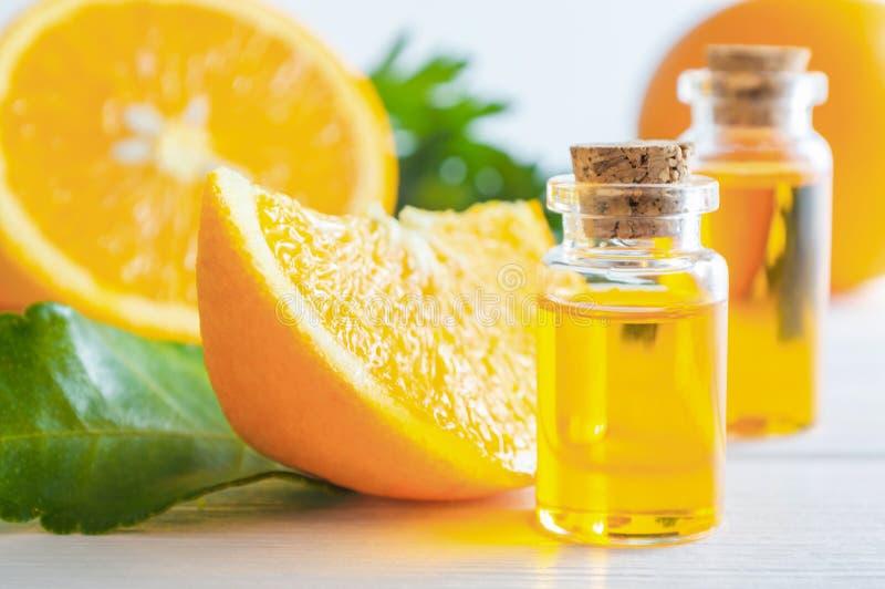 Óleo essencial alaranjado natural na garrafa e no fruto das laranjas do corte na tabela de madeira branca foto de stock royalty free