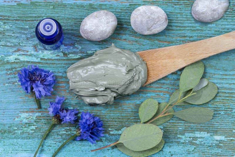 Óleo essencial com argila e centáurea cosméticas e ramo do eucalipto, pedras, para tratamentos dos termas, na colher de madeira,  imagens de stock
