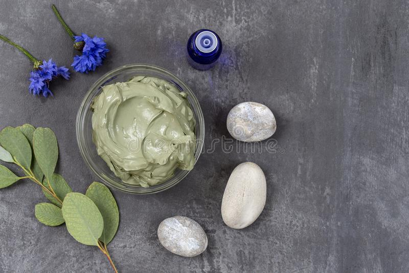 Óleo essencial com argila e a flor cosméticas e ramo do eucalipto, pedras, para tratamentos dos termas, na bacia de vidro no cinz foto de stock royalty free