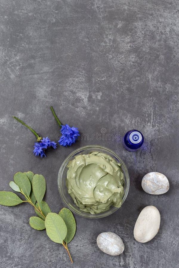 Óleo essencial com argila e a flor cosméticas e ramo do eucalipto, pedras, para tratamentos dos termas, na bacia de vidro no cinz fotografia de stock