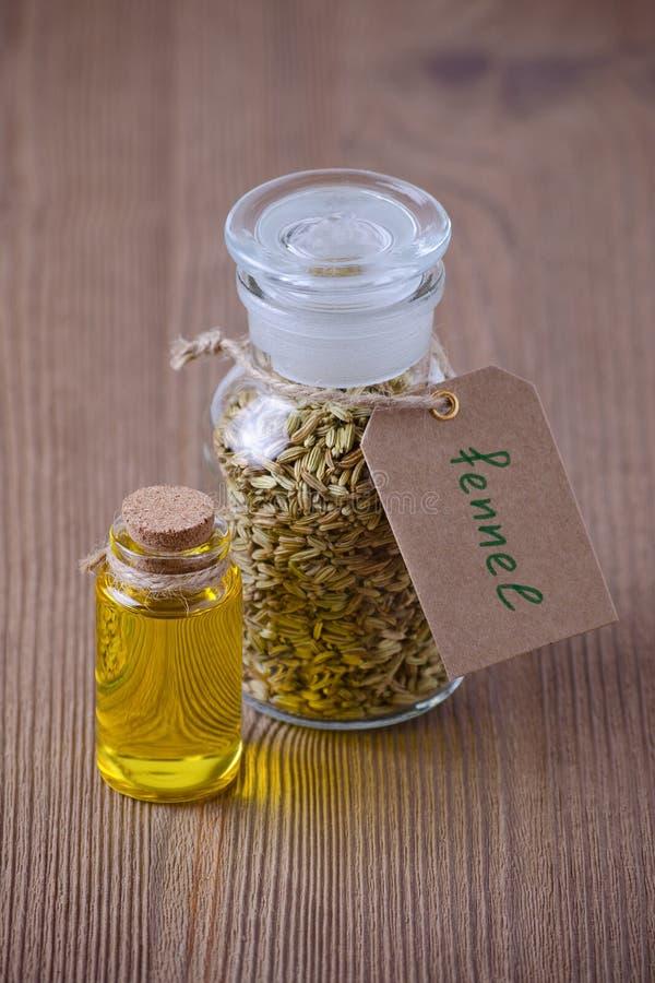 Óleo essencial da erva-doce e uma garrafa com sementes, foco seletivo em de madeira escuro fotos de stock royalty free