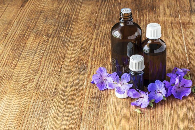 Óleo essencial do prado do gerânio em uns recipientes de vidro escuros no fundo de madeira com flores e folhas Foco seletivo fotografia de stock