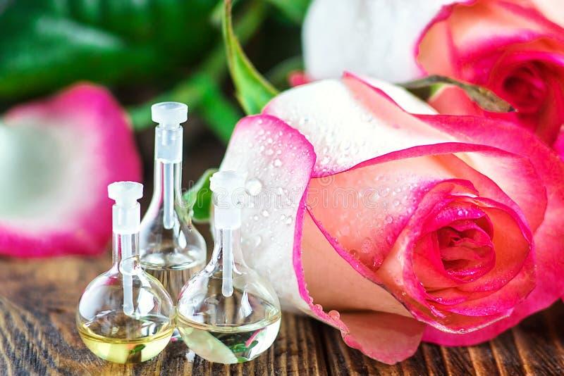 Óleo essencial na garrafa de vidro com as flores cor-de-rosa no fundo de madeira Garrafas pequenas do perfume Tratamento da belez fotografia de stock royalty free