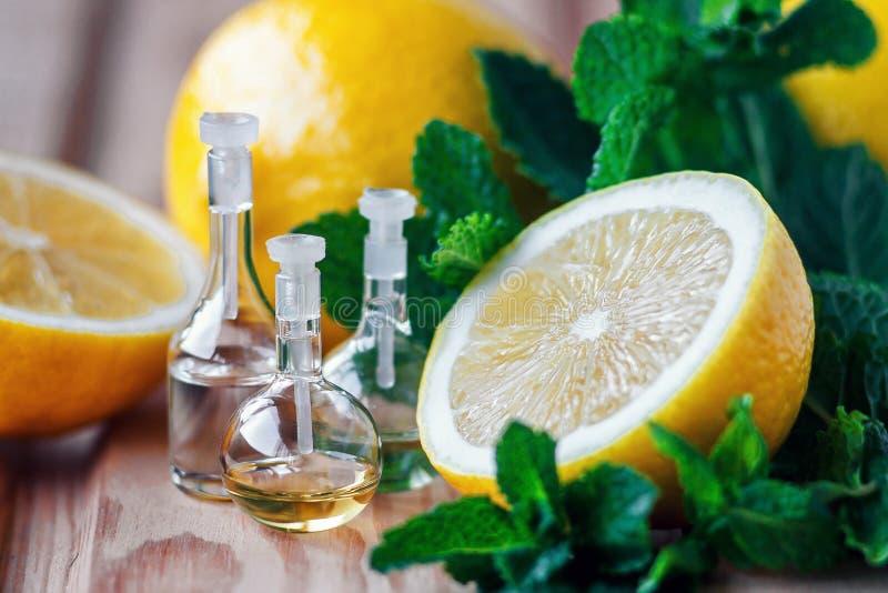 Óleo essencial na garrafa de vidro com fruto fresco, suculento do limão e as folhas verdes da hortelã no fundo de madeira Tratame fotografia de stock royalty free