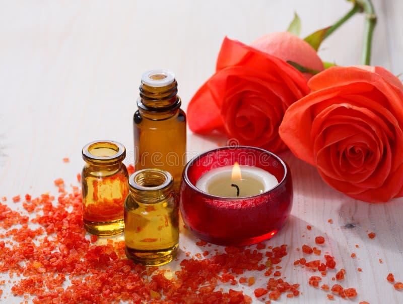 Óleo essencial, sais de banho minerais, vela e flores imagem de stock