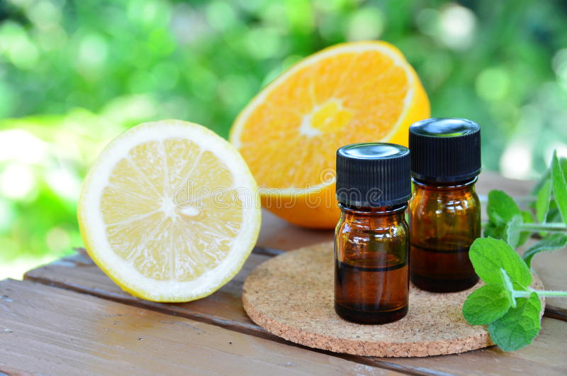 Óleos essenciais com citrinas e ervas fotos de stock royalty free