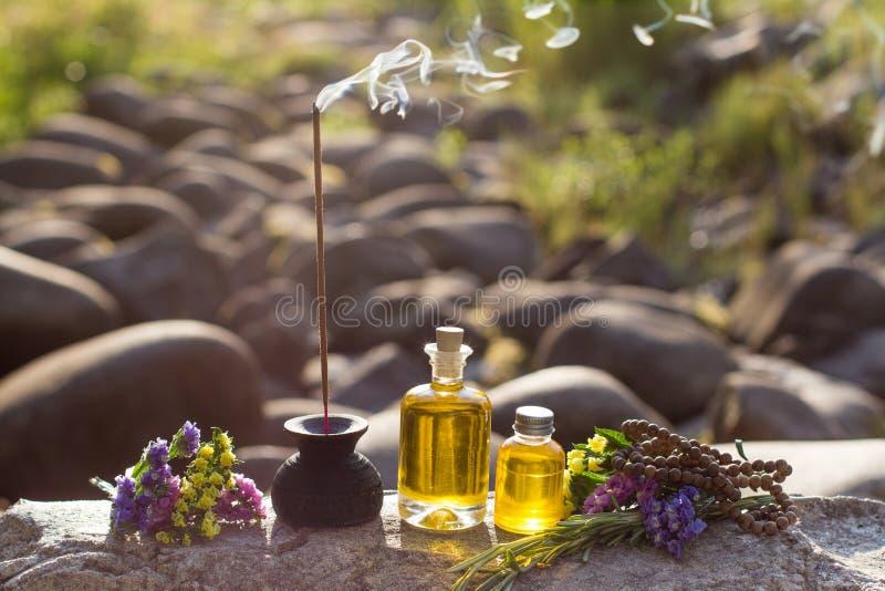 Óleos essenciais e varas aromáticas para a meditação em uma rocha imagens de stock