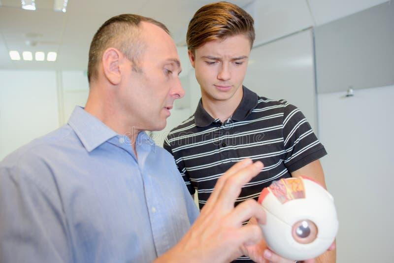 Óptico con el hombre joven que sostiene el ojo modelo foto de archivo