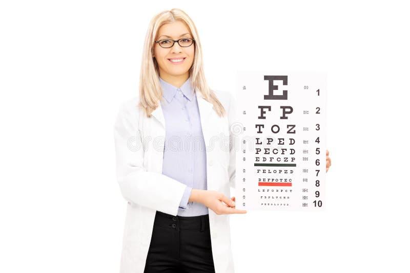 Óptico femenino que lleva a cabo la prueba de la vista imagen de archivo