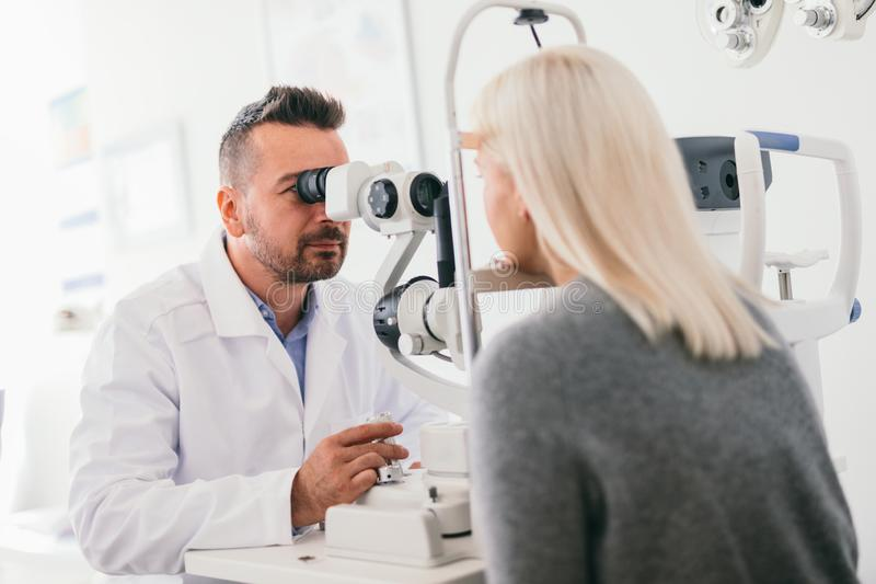 Óptico que comprueba los ojos de su paciente fotografía de archivo