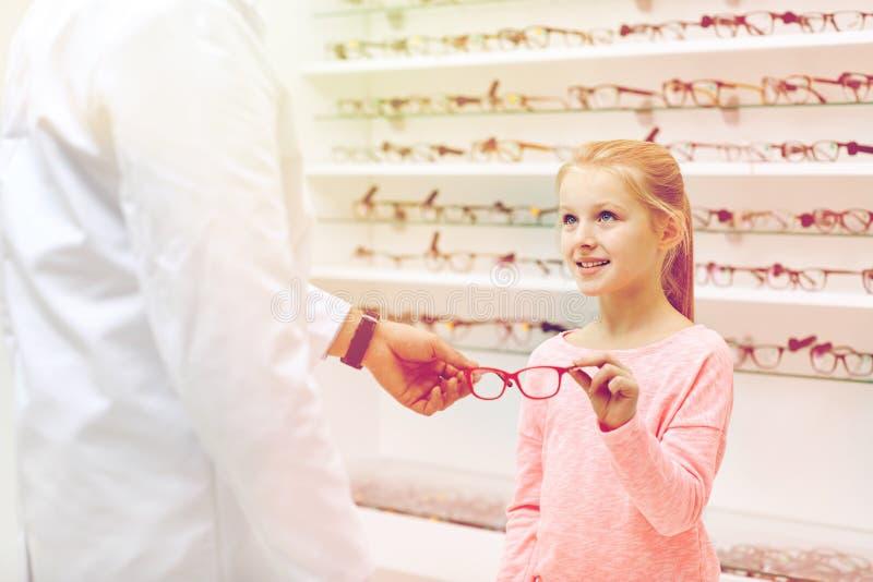 Óptico que da los vidrios a la muchacha en la tienda de la óptica imagen de archivo