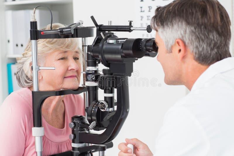 Óptico que examina al paciente femenino mayor a través de la lámpara rajada foto de archivo