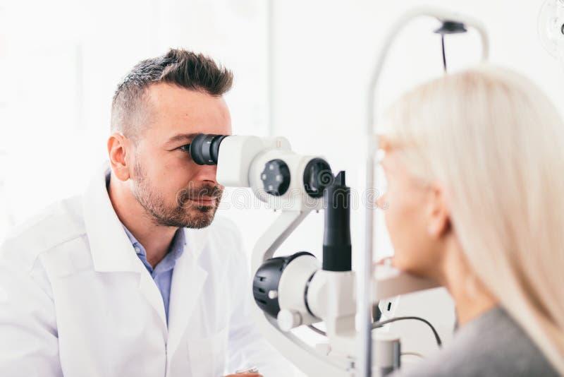Óptico que examina su vista de los pacientes fotografía de archivo libre de regalías