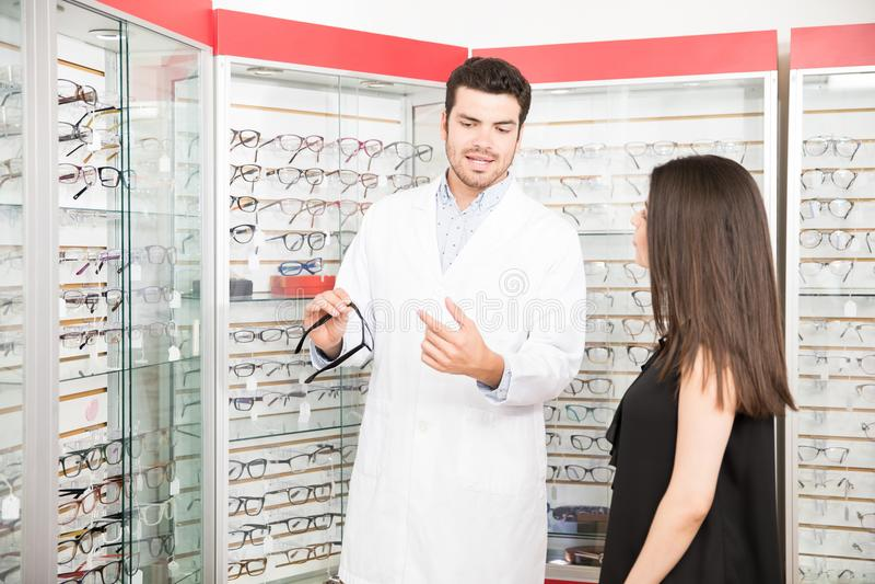 Óptico que muestra los vidrios a la mujer en la tienda de la óptica foto de archivo libre de regalías