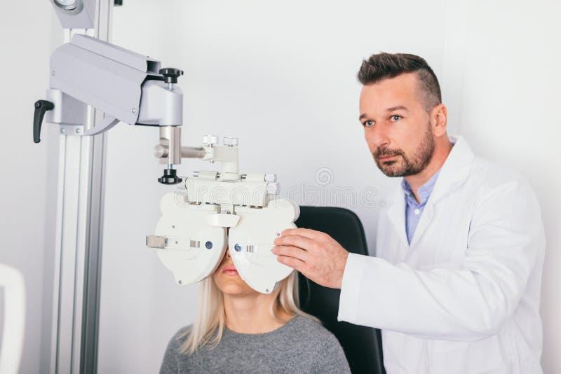 Óptico que prueba los ojos de su paciente foto de archivo libre de regalías