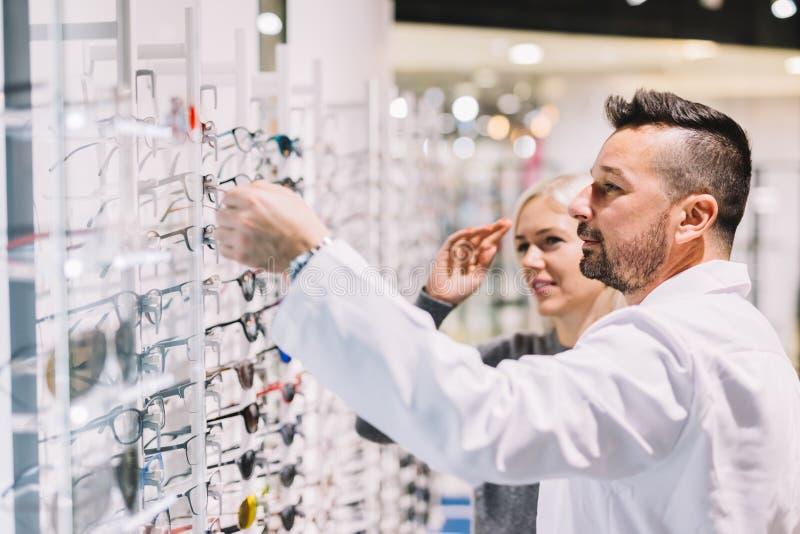 Óptico y su paciente que eligen los vidrios foto de archivo