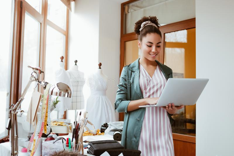 Órdenes en línea por el correo electrónico El sastre de la mujer joven con el ordenador portátil está contestando a correos elect fotos de archivo libres de regalías