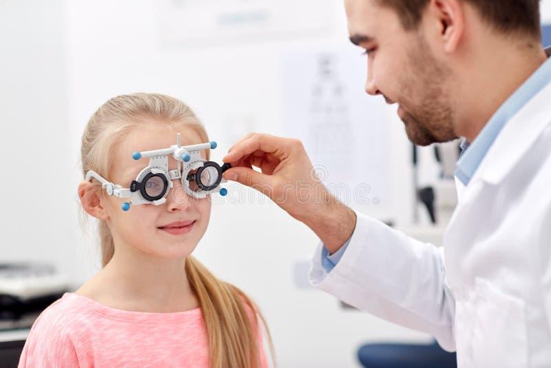 Ótico com quadro experimental e menina na clínica foto de stock