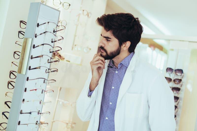 Ótico do homem no revestimento na loja do sistema ótico fotos de stock royalty free