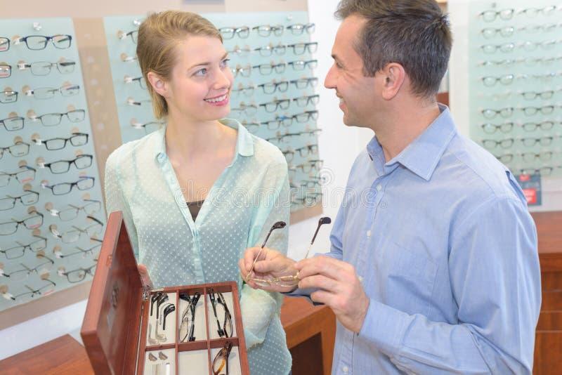 Ótico fêmea que mostra vidros ao homem na loja do sistema ótico fotos de stock royalty free