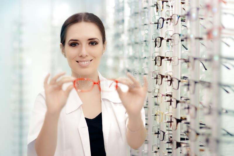 Ótico feliz Handing Over Eyeglasses para uma tentativa fotos de stock
