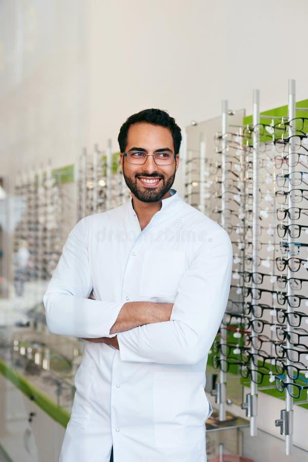 Ótico Man Near Showcase com os monóculos na loja dos vidros fotos de stock royalty free