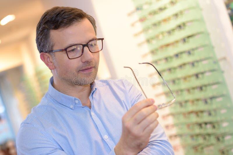 Ótico que mostra vidros ao homem na loja do sistema ótico foto de stock royalty free